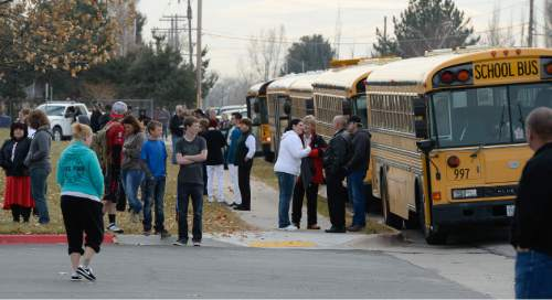 Francisco Kjolseth  |  The Salt Lake Tribune People gather on the edge of Fremont High school in Plain City during a lock down after reports of a student seen with a gun on Monday, Dec. 1, 2014.