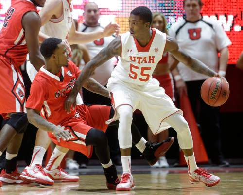 Ball State's Zavier Turner (1) falls as he guards Utah's Delon Wright (55) during the first half of an NCAA college basketball game Friday, Nov. 14, 2014, in Salt Lake City. (AP Photo/Rick Bowmer)