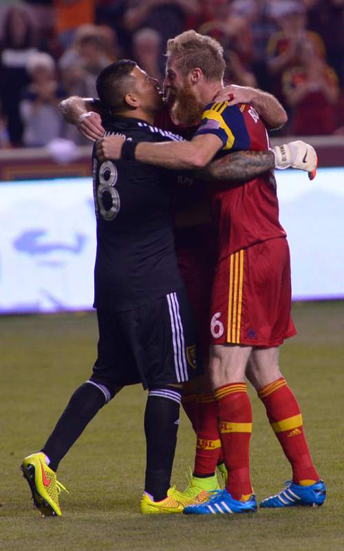 Leah Hogsten     The Salt Lake Tribune Real Salt Lake goalkeeper Nick Rimando (18) celebrates his new MLS record for career game shutouts at 113 with Real Salt Lake defender Nat Borchers (6) and Real Salt Lake midfielder Kyle Beckerman (5).  Real Salt Lake defeated D. C. United 3-0 Saturday, August 9, 2014, at Rio Tinto Stadium.