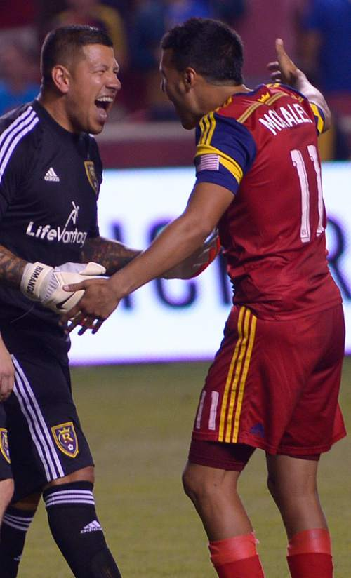 Leah Hogsten     The Salt Lake Tribune Real Salt Lake goalkeeper Nick Rimando (18) celebrates his new MLS record for career game shutouts at 113 with Real Salt Lake midfielder Javier Morales (11). Real Salt Lake defeated D. C. United 3-0 Saturday, August 9, 2014, at Rio Tinto Stadium.