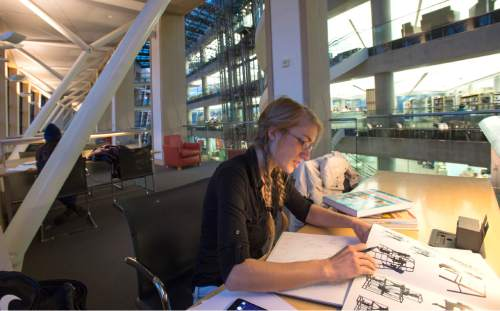 Rick Egan  |  The Salt Lake Tribune  Amanda Kochenash works on a project in the Salt Lake City Library, Monday, December 8, 2014. There is a proposal to keep the first two floors of the Salt Lake Public Library open 24/7, including the reading area on the south side.