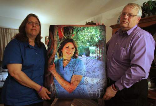 Rick Egan   |  The Salt Lake Tribune  Judy and Chuck Cox, mother and father of Susan Powell, hold a photo of Susan Powell, that has been signed by supporters, during an interview in their home in Puyallup, Washington,  Wednesday, November 3, 2010.
