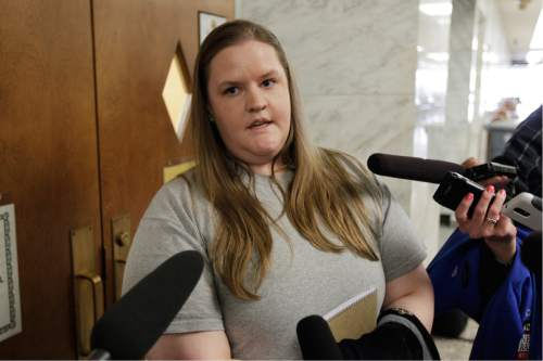 Steve Powell's daughter Alina Powell talks to reporters following a court hearing for her father, Steve Powell, Monday, April 23, 2012, in Tacoma, Wash. Alina Powell defended her father outside of court, saying that evidence against him in his upcoming voyeurism trial has been fabricated. (AP Photo/Ted S. Warren)