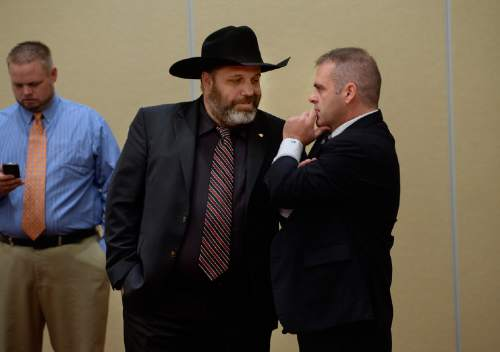 Scott Sommerdorf   |  The Salt Lake Tribune Rick Koerber, center, confers with his attorney Marcus Mumford, right prior to speaking at a news conference the day after a federal judge tossed out 18 charges against Koerber that had alleged he operated a giant Ponzi scheme through his real estate company, Friday, August 15, 2014.