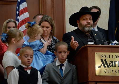 Scott Sommerdorf   |  The Salt Lake Tribune Rick Koerber speaks at a news conference supported by family. His daughter Bethany is at far left, two adopted sons, Erick and Samuel in the foreground, and his wife Jewel Skousen holds their daughter Annastasia the day after a federal judge tossed out 18 charges against Koerber that had alleged he operated a giant Ponzi scheme through his real estate company, Friday, August 15, 2014.