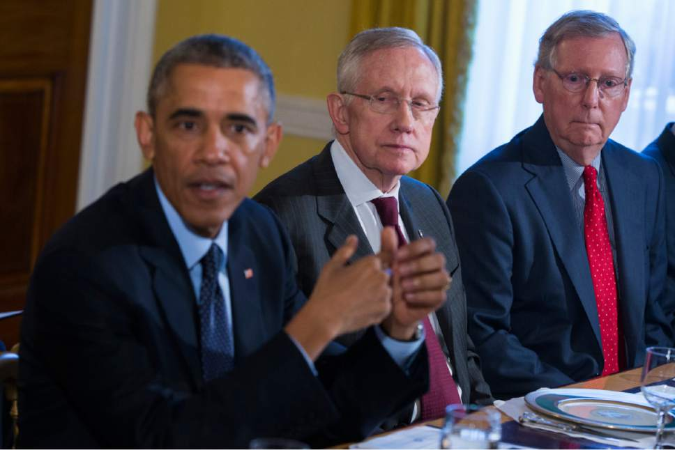 Senate Minority Leader Mitch McConnell of Ky., right, and Senate Majority Leader Harry Reid of Nev., center, listen as President Barack Obama speaks during a meeting with Congressional leaders in the Old Family Dining Room of the White House in Washington, Friday, Nov. 7, 2014. (AP Photo/Evan Vucci)
