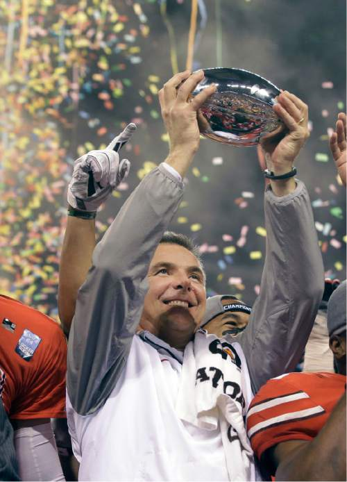 Ohio State head coach Urban Meyer holds up the championship trophy after defeating the Wisconsin Badgers 59-0 in the Big Ten Conference championship NCAA college football game after midnight Sunday, Dec. 7, 2014, in Indianapolis. Ohio State won 59-0. (AP Photo/Darron Cummings)