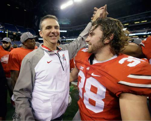 Ohio State head coach Urban Meyer, left, celebrates with linebacker Craig Fada and the rest of the Buckeyes after defeating Wisconsin in the Big Ten Conference championship NCAA college football game after midnight Sunday, Dec. 7, 2014, in Indianapolis. Ohio State won 59-0. (AP Photo/Darron Cummings)