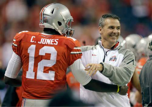 Ohio State head coach Urban Meyer, right, smiles along side quarterback Cardale Jones during the second half of the Big Ten Conference championship NCAA college football game against Wisconsin Saturday, Dec. 6, 2014, in Indianapolis. (AP Photo/Darron Cummings)