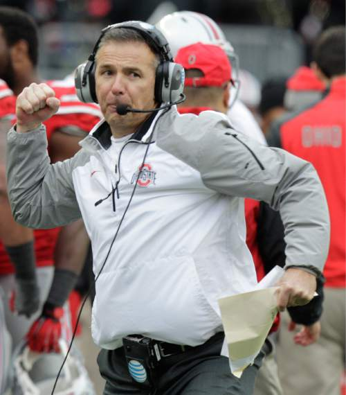 Ohio State head coach Urban Meyer reacts to an Ohio State touchdown against Michigan during the fourth quarter of an NCAA college football game Saturday, Nov. 29, 2014, in Columbus, Ohio. Ohio State beat Michigan 42-28. (AP Photo/Jay LaPrete)