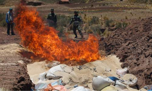 "In this Nov. 7, 2014 photo, soldiers burn bags of Peruvian quinoa in Guaqui, Bolivia. The decrease in quinoa prices are worrying for Bolivia's small-scale organic quinoa farmers, who can't produce the crop as cheaply as their Peruvian competitors that grow factory-farmed quinoa and use pesticides. ""There is so much supply on the market because of Peru's big production that prices simply must go down,"" said Pablo Laguna, a Bolivian anthropologist and quinoa expert. ""The price downturn is irreversible."" (AP Photo/Juan Karita)"