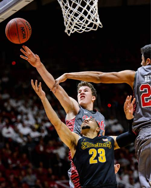 Trent Nelson  |  The Salt Lake Tribune Utah Utes forward Jakob Poeltl (42) blocks a shot by Wichita State Shockers guard Fred VanVleet (23) as the University of Utah Utes host the Wichita State Shockers, college basketball at the Huntsman Center in Salt Lake City, Wednesday December 3, 2014. Utah Utes forward Chris Reyes (20) at right.