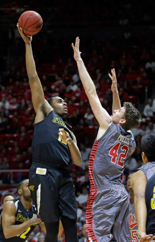 Wichita State forward Darius Carter (12) shoots as Utah forward Jakob Poeltl (42) defends in the second half of an NCAA college basketball game Wednesday, Dec. 3, 2014, in Salt Lake City. (AP Photo/Rick Bowmer)