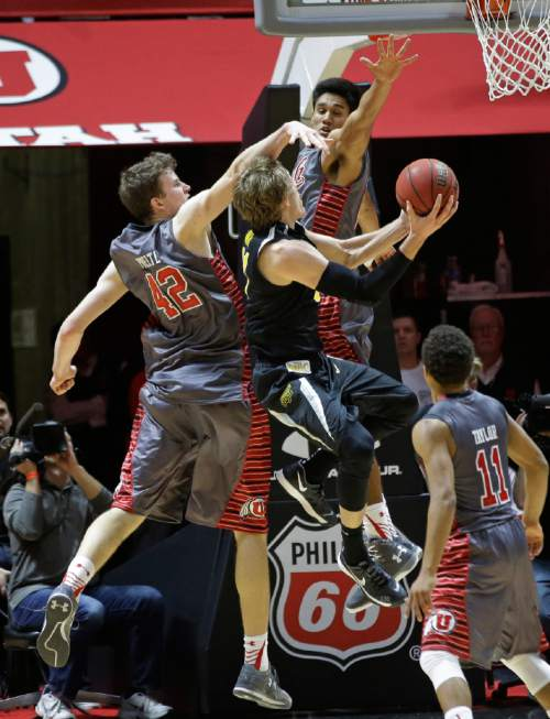 Wichita State guard Ron Baker, center, drives to the basket as Utah's Chris Reyes, rear, and Jakob Poeltl (42) defend in overtime during an NCAA college basketball game Wednesday, Dec. 3, 2014, in Salt Lake City. Utah won 69-68. (AP Photo/Rick Bowmer)