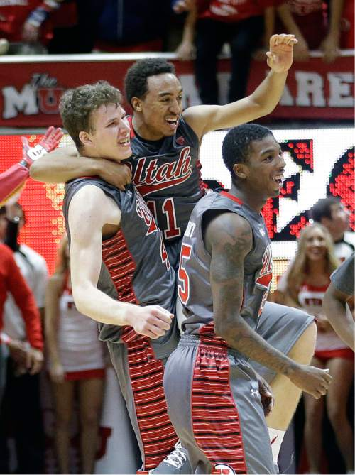 Utah Brandon Taylor, center, celebrates with Jakob Poeltl (42) and Delon Wright following an NCAA college basketball game against Wichita State, Wednesday, Dec. 3, 2014, in Salt Lake City. Utah won 69-68. (AP Photo/Rick Bowmer)