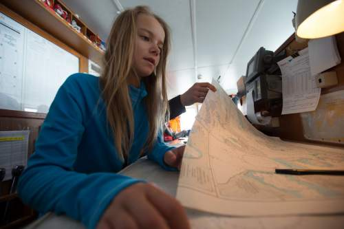Lilliana Libecki, 11, studies maps of Antarctica while boating through the Drake Passage on her way to ski the South Pole and hang out with penguins. photos courtesy Mike Schirf