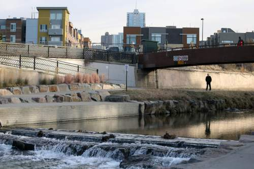 In this Dec. 8, 2014 photo, pedestrians pass through Confluence Park, where Cherry Creek joins the South Platte, a key channel in Colorado's water supply, in Denver. Colorado is drawing up a strategy to protect some of the trillions of gallons of water that gushes out of the Rocky Mountains every spring as the snow melts, most of which flows into drought-stricken California and other states. (AP Photo/Brennan Linsley)