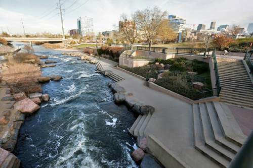 In this Monday, Dec. 8, 2014 photo, water flows past a sculpted landscape at Confluence Park, where Cherry Creek joins the South Platte, a key channel in Colorado's water supply, in Denver. Colorado is drawing up a strategy to protect some of the trillions of gallons of water that gushes out of the Rocky Mountains every spring as the snow melts, most of which flows into drought-stricken California and other states. (AP Photo/Brennan Linsley)