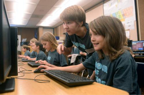 Al Hartmann  |  The Salt Lake Tribune Sixth-graders at Layton Elementary School get an introduction to computer programing during the annual Pluralsight Hour of Code event Tuesday Dec. 9, 2014. Riverton HIgh School junior Katya Eames, center, on the Pluralsight development team, coaches Sophie Mee.