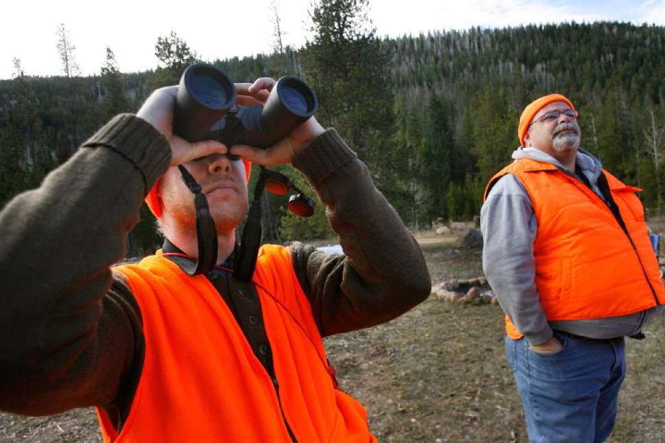 Scott Sommerdorf  |  The Salt Lake Tribune               Nicholas Smith, left, scans the hillsides near Kamas for deer as Shawn Gehring, right, looks on, Saturday, October 19, 2012. The general season rifle deer hunt opened at dawn Saturday with a new format that limits hunters to one of 30 units instead of one of five regions in the state. More than 52,000 are expected to be in the field.