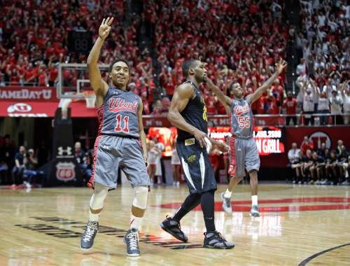 Utah guard Brandon Taylor (11) celebrates after hitting a 3-point shot as Wichita State guard Tekele Cotton, center, looks away in the second half during an NCAA college basketball game Wednesday, Dec. 3, 2014, in Salt Lake City. Utah won 69-68 in overtime. (AP Photo/Rick Bowmer)