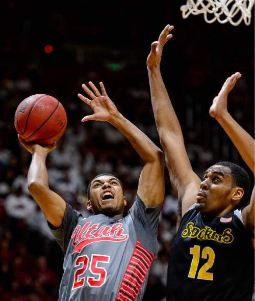 Trent Nelson  |  The Salt Lake Tribune Utah Utes guard Kenneth Ogbe (25) looks for a shot, defended by Wichita State Shockers forward Darius Carter (12) as the University of Utah Utes host the Wichita State Shockers, college basketball at the Huntsman Center in Salt Lake City, Wednesday December 3, 2014.