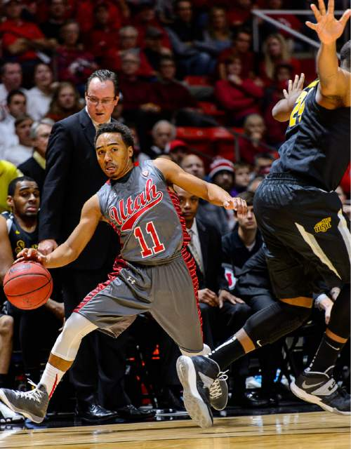 Trent Nelson  |  The Salt Lake Tribune Utah Utes guard Brandon Taylor (11) tries to stay in bounds, going around Wichita State Shockers forward Shaquille Morris (24) as the University of Utah Utes host the Wichita State Shockers, college basketball at the Huntsman Center in Salt Lake City, Wednesday December 3, 2014.