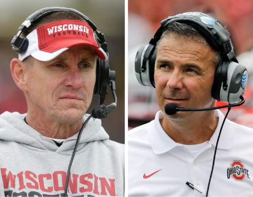 FILE - At left, in a Nov. 8, 2014, file photo, Wisconsin head coach Gary Andersen looks on during an NCAA college football game against Purdue in West Lafayette, Ind. At right, in an Aug. 30, 2014, file photo, Ohio State head coach Urban Meyer walks on the field in the second half of an NCAA college football game against Navy in Baltimore. Coaches and players say walk-ons like Ohio Stateís Kosta Karageorge _ who was found dead of an apparently self-inflicted gunshot on Sunday, Nov. 30, 2014, are treated just as well as their highly recruited teammates. Meyer and Andersen, the opposing coaches in Saturday's Big Ten championship game, believe things have gotten better since their own walk-on experiences. Meyer walked on at Cincinnati in the 1980s at the same time that Anderson was walking on at Ricks College. Andersen said he tries to make sure walk-ons are treated the same as his scholarship players. (AP Photo/File)