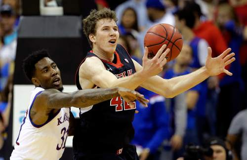 Kansas' Jamari Traylor left, and Utah's Jakob Poeltl chase a loose ball during the first half of an NCAA college basketball game Saturday, Dec. 13, 2014, in Kansas City, Mo. (AP Photo/Charlie Riedel)