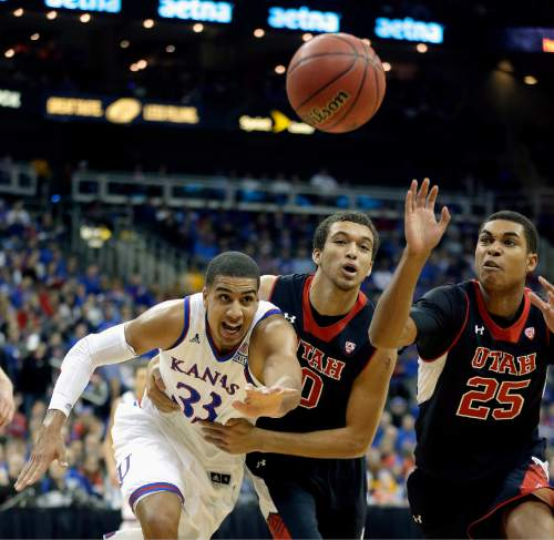 Kansas' Landen Lucas (33), Utah's Brekkott Chapman (0) and Kenneth Ogbe (25) chase a loose ball during the first half of an NCAA college basketball game Saturday, Dec. 13, 2014, in Kansas City, Mo. (AP Photo/Charlie Riedel)