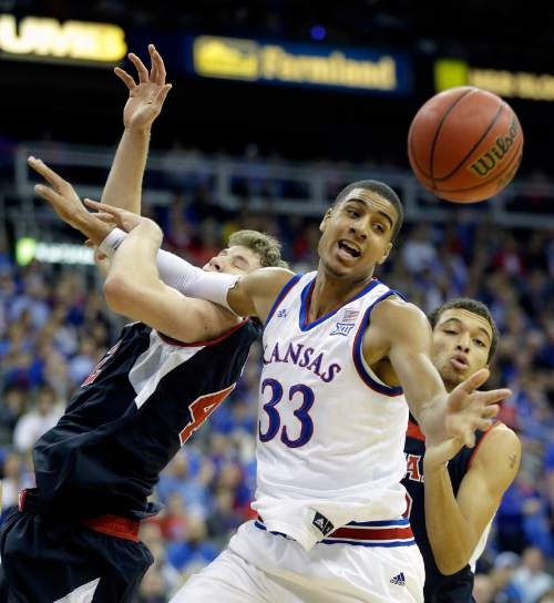 Kansas' Landen Lucas (33) battles Utah's Jakob Poeltl, left, and Brekkott Chapman, right, for a loose ball during the first half of an NCAA college basketball game, Saturday, Dec. 13, 2014, in Kansas City, Mo. (AP Photo/Charlie Riedel)