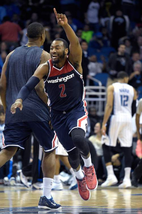 Washington Wizards guard John Wall (2) celebrates after teammate Bradley Beal tipped in the game-winning basket as time expired at the end of the second half of an NBA basketball game against the Orlando Magic in Orlando, Fla., Wednesday, Dec. 10, 2014. The Wizards won 91-89. (AP Photo/Phelan M. Ebenhack)