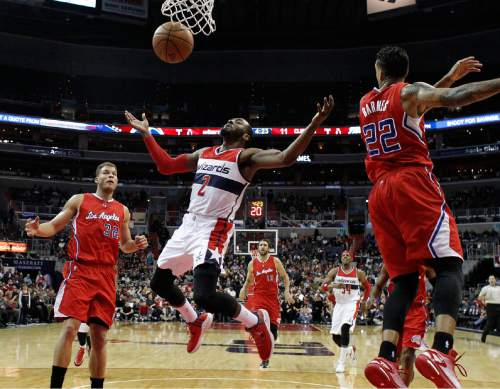 Washington Wizards guard John Wall (2) loses control of the ball between Los Angeles Clippers forward Blake Griffin (32) and forward Matt Barnes (22) in the first half of an NBA basketball game, Friday, Dec. 12, 2014, in Washington. (AP Photo/Alex Brandon)