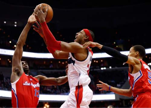 Los Angeles Clippers forward Ekpe Udoh (13) and guard Jared Cunningham (9) combine on Washington Wizards forward Paul Pierce (34) in the second half of an NBA basketball game, Friday, Dec. 12, 2014, in Washington. The Wizards won 104-96. (AP Photo/Alex Brandon)
