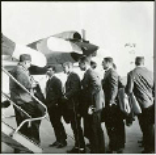 Courtesy  |  Utah Athletics  Looking smart in jackets specially tailored for the occasion, Utah's 1964 Liberty Bowl-winning team prepares to board the plane.