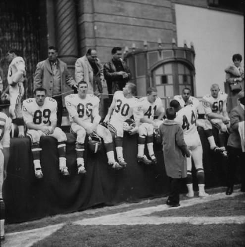 Courtesy  |  Utah Athletics  Utah players William Morley (No. 89), Merlin Driggs (No. 86), John McQuaide (No. 30), John Collins (No. 41), Andy Ireland (No. 44) and Pat McKissick (No. 50) sit on the Atlantic City Convention Hall stage at the 1964 Liberty Bowl at Atlantic City Convention Hall on Dec. 19, 1964.