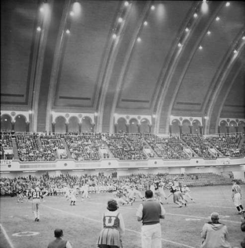 Courtesy  |  Utah Athletics  Utah, in white, plays West Virginia in the 1964 Liberty Bowl, the first-ever college bowl game played indoors. The lights on the Atlantic City Convention Hall dome were a challenge for punt returners, who would lose the ball in the brightness.