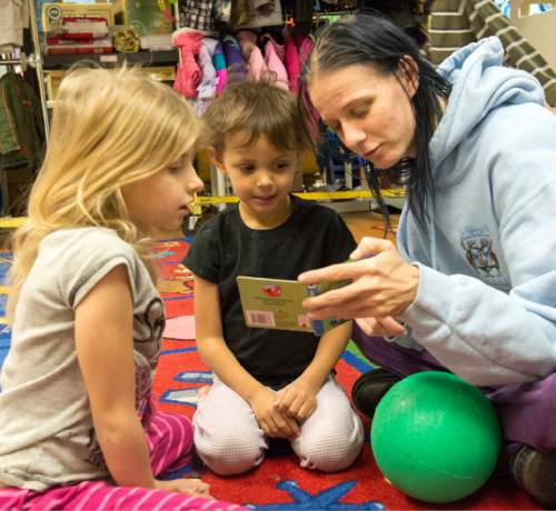 Rick Egan     The Salt Lake Tribune Grace Chilton, 7, and Starr, 3, read a book with their mother, Amie Chilton, at the Road Home shelter on Friday.