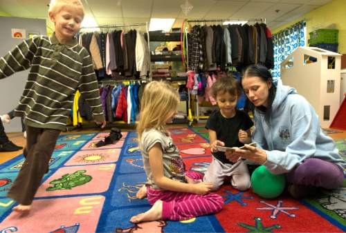Rick Egan  |  The Salt Lake Tribune  TãShawn Chilton, 5 (left) runs in circles as  Grace 7, and Starr, 3, read a book with their mother,  Amie Chilton, at the Road Home shelter,  Friday, November 28, 2014