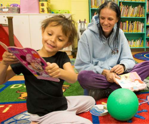 Rick Egan  |  The Salt Lake Tribune  Starr Chilton, 3, reads a book with her mother,  Amie Chilton, at the Road Home shelter,  Friday, November 28, 2014