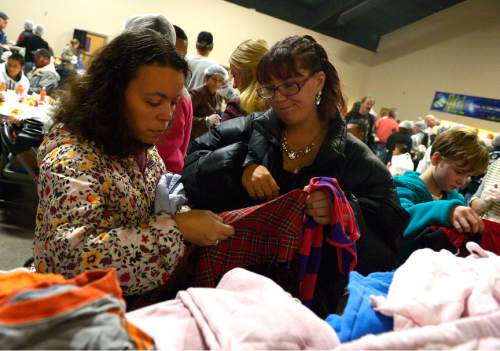 Leah Hogsten  |  The Salt Lake Tribune l-r Jessica Aponte and Toni Webb check clothing sizes while looking for clothes for themselves and their daughters after their midday Thanksgiving dinner. The Salt Lake City Mission provided Thanksgiving meals at the Christian Life Center, Thursday, November 27, 2014 in Salt Lake City.