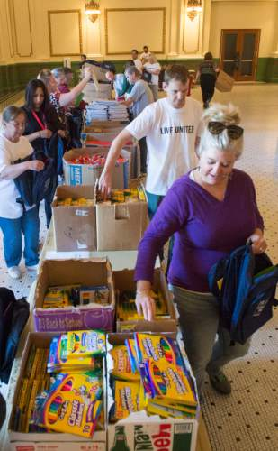 Rick Egan  |  The Salt Lake Tribune  Volunteers help fill 8,500 backpacks with school supplies for low-income kids in the Grand Hall at the Gateway, during United Way of Salt Lake's 22nd annual Day of Caring, Thursday, September 11, 2014.  More than 5,500 volunteers from over 125 companies participated in 130 service projects throughout  Davis, Salt Lake, Summit and Tooele counties today.