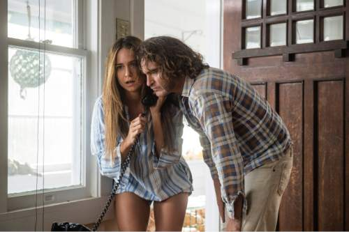 """This photo provided by Warner Bros. Pictures shows Joaquin Phoenix, right, as Larry """"Doc"""" Sportello, and Katherine Waterston as Shasta Fay Hepworth in Warner Bros. Pictures' and IAC Films' """"Inherent Vice,"""" a Warner Bros. Pictures release. The film releases on Dec. 12, 2014. (AP Photo/Warner Bros. Pictures, Wilson Webb)"""
