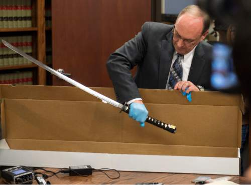 Steve Griffin     The Salt Lake Tribune  Utah County Attorney Bureau of Investigations Bureau Chief Jeff Robinson removes the sword carried by Darrien Hunt as Utah County Attorney Jeffrey Buhman addresses the media as he explains the Utah County Attorney Office's ruling in the officer-involved shooting of Hunt during a press conference in Provo, Monday, November 3, 2014.