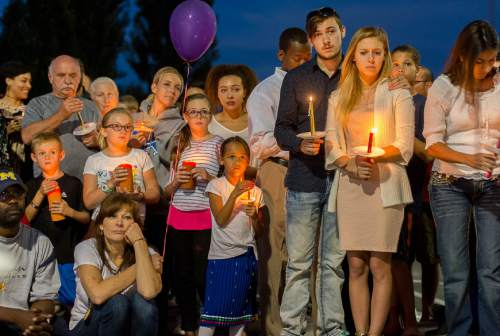 Trent Nelson     The Salt Lake Tribune Susan Hunt, lower left, listens to stories about her son, Darrien Hunt, at a candlelight vigil Sunday September 14, 2014 for Darrien, who was shot and killed by Saratoga Springs police.