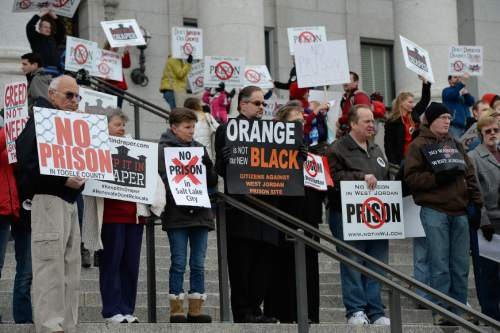 "Francisco Kjolseth  |  The Salt Lake Tribune Chris Connell of West Jordan, center holding ""Orange Is Not Our New Black"" sign joins the protest and is upset that the W. Jordan site would be 3,000 feet from his home. The five community groups opposing the prison relocation protested at noon, on the outh steps of the Utah Capitol on Monday, Dec. 22, 2014, two hours before the Prison Relocation Commission meeting."