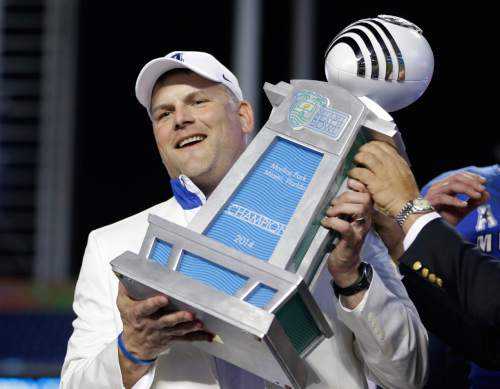 Memphis head coach Justin Fuente holds up the trophy after Memphis defeated Brigham Young 55-48 in double overtime during the inaugural Miami Beach Bowl football game, Monday, Dec. 22, 2014 in Miami. (AP Photo/Wilfredo Lee)