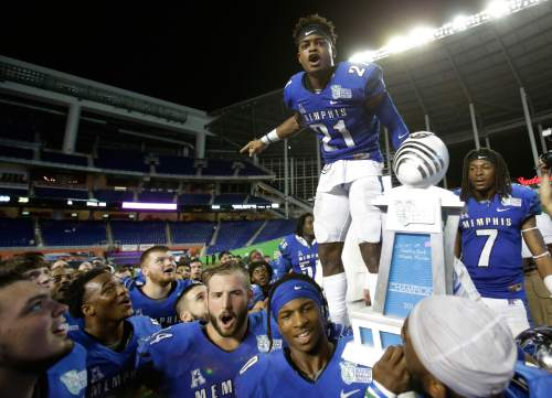 Memphis defensive back Bobby McCain (21) celebrates with the team after Memphis defeated Brigham Young, 55-48 in double overtime during the inaugural Miami Beach Bowl football game, Monday, Dec. 22, 2014, in Miami. (AP Photo/Wilfredo Lee)