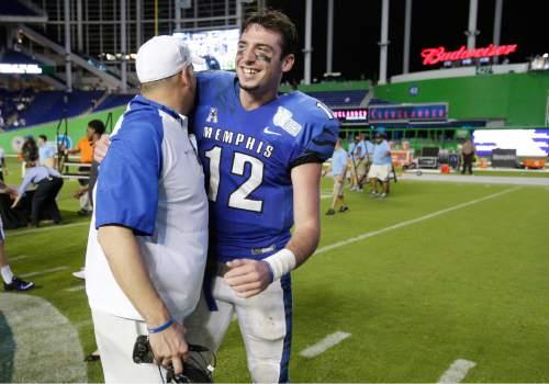 Memphis head coach Justin Fuente, left, congratulates quarterback Paxton Lynch after Memphis won the inaugural Miami Beach Bowl football game against Brigham Young, Monday, Dec. 22, 2014 in Miami. (AP Photo/Wilfredo Lee)