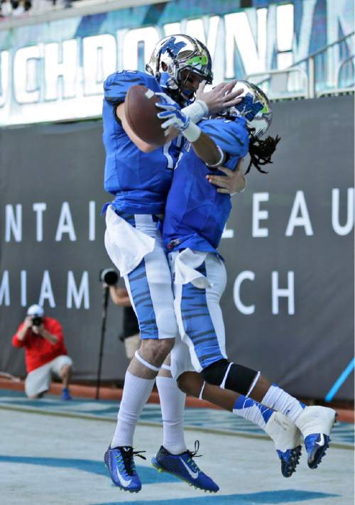 Memphis wide receiver Keiwone Malone, right, celebrates a touch down pass with quarterback Paxton Lynch during the first half of the in the inaugural Miami Beach Bowl football game against Brigham Young, Monday, Dec. 22, 2014 in Miami. (AP Photo/Wilfredo Lee)